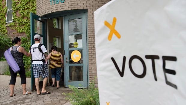 Voters arrive at a polling station in Toronto to cast their vote for the Ontario provincial election on Thursday, June 12, 2014.