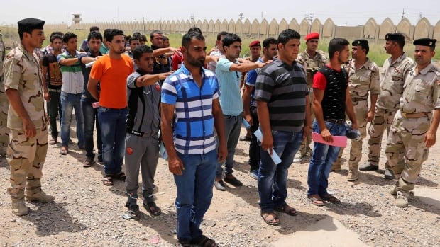 Iraqi men line up outside a military base in hopes of joining the fledging army. Islamic Front militants have posted videos online of violent executions in an effort to dissuade new recruits from enlisting.