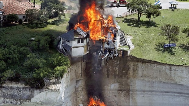 Smoke rises from a house deliberately set on fire, days after part of the ground it was resting on collapsed into Lake Whitney, in Texas. Building crews set fire on Friday to the luxury lake house left dangling about 23 metres on a decaying cliff that has been giving way underneath the structure.