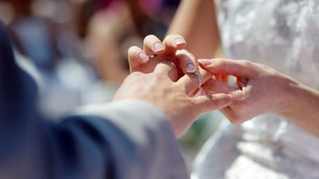Bride putting a wedding ring on groom's finger 59745521