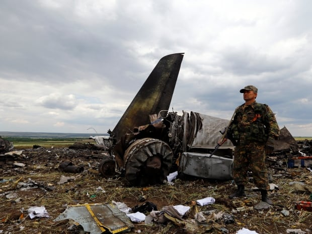 An armed pro-Russian separatist stands guard at the site of the crash of the Il-76 Ukrainian army transport plane in Luhansk on June 14, 2014. Pro-Russian separatists shot down the transport plane with an anti-aircraft missile as it came in to land early on Saturday.