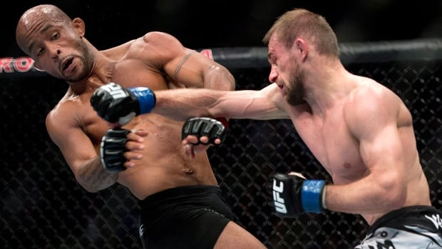American Demetrious Johnson, left, ducks from a punch by Russia's Ali Bagautinov during the flyweight bout at UFC 174 in Vancouver on Saturday night. Johnson scored a unanimous decision to retain the title.