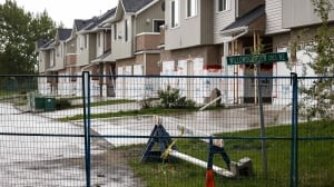 A fence cordons off condemned houses that will be demolished one year after a devastating flood in High River, Alta.