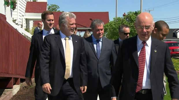Quebec Premier Philippe Couillard, along with cabinet ministers Yves Bolduc, (centre), and  Jacques Daoust, were in Port-Cartier, Que. on June 16, 2014 to announce FerroAtlantica's intention to build a silicon metal plant.