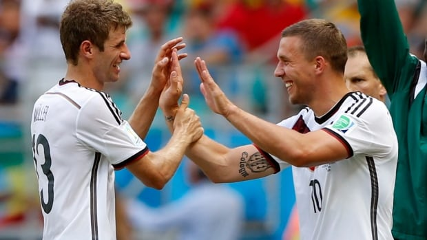 Germany's Thomas Mueller, left, is greeted by Lukas Podolski  during the group G World Cup soccer match between Germany and Portugal in Salvador, Brazil, on Monday.