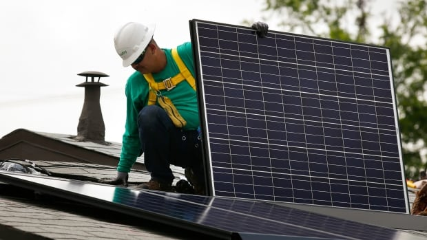 A SolarCity Corp. employee installs a solar panel on the roof of a home in Los Angeles. The company bought one of America's largest panel-makers Tuesday.