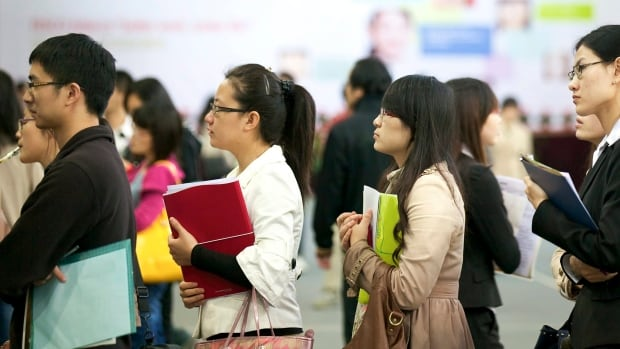 Chinese college students wait in line at a job fair. A new study finds job applicants from more modest cultures, including the Chinese, do not get high ratings in job interviews.