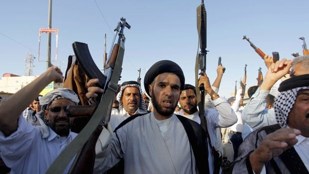 Tribal fighters shout slogans as they carry weapons during a parade in the streets of Najaf, south of Baghdad, on Tuesday. Iraq's Shia rulers defied Western calls on Tuesday to reach out to Sunnis to defuse the uprising in the north of the country. The sectarian split goes back more than 1,300 years.