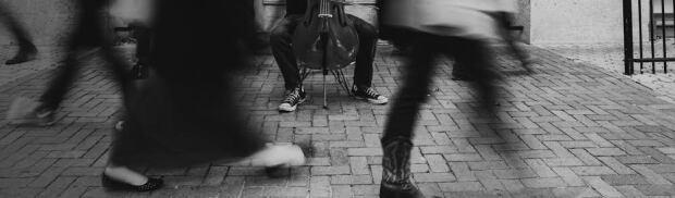Cellist on street wearing sneakers