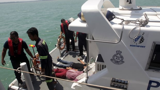 Malaysian marine police officers stand on the deck of a boat after retrieving bodies of a capsized boat off Sungai Air Hitam in Banting, outside Kuala Lumpur, on Wednesday. At least 60 people survived when a wooden boat carrying 97 Indonesians capsized and sank.
