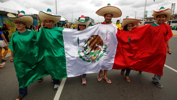 Mexican fans walk to the Arena Castelao draped in their national flag before the group A World Cup soccer match between Brazil and Mexico on Tuesday. In Windsor, police warn partiers to be safe.  (AP Photo/Eduardo Verdugo)