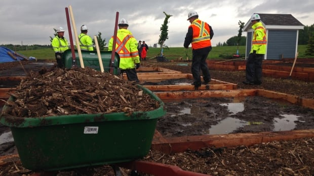 About 100 volunteers slogged through the rain to build a brand new community garden in Meadowgreen.