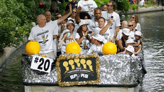 Spurs head coach Gregg Popovich waves to the fans during the victory parade down the River Walk on Wednesday in San Antonio, Tex. The Spurs' championship over Miami is its fifth and first since 2007.