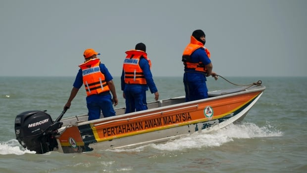 Members of Malaysian Civil Defense Department on a speed boat search for missing Indonesians of a sunken boat off west coast in Banting, outside Kuala Lumpur, Malaysia, Thursday. Another overcrowded wooden boat on Wednesday carrying Indonesian illegal immigrants home sank in choppy seas, with 25 people still missing. Ten people died in that accident, but at least 62 people survived.