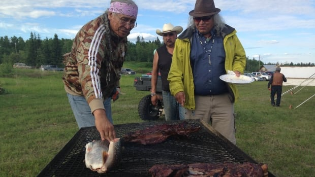 Dene elder Francois Paulette (left) told stories of resettling in Fort Fitzgerald, Alta. as part of a ceremony marking the 115th anniversary of the signing of Treaty 8 by Chief Pierre Squirrel of the Smith's Landing First Nation. It was the opening event for the 2014 Dene National Assembly underway in Fort Smith, N.W.T.