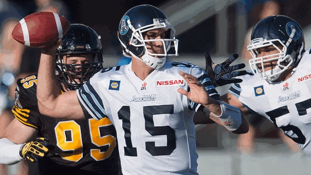 Argonauts quarterback Ricky Ray makes a pass while under pressure from Tiger-Cats' Brian Bulcke, left, and teammate Tyler Holmes in the first quarter of Thursday's CFL pre-season game at Varsity Stadium. Toronto won 41-23 in the final exhibition contest for both teams.