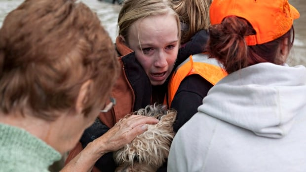 A resident is comforted by rescuers as she clutches her dog after being retrieved from the floodwaters in High River, Alta. on June 20, 2013, after the Highwood River overflowed its banks.