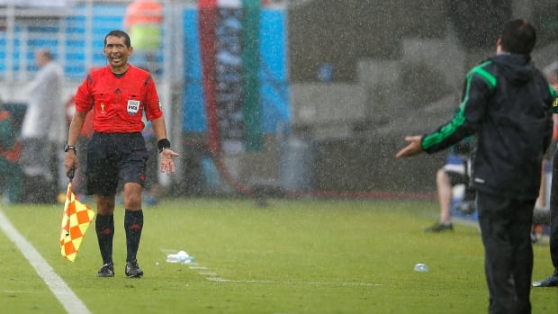 Assistant referee Humberto Clavijo, left, argues with Mexico's head coach Miguel Herrera during the first half of the Cameroon-Mexico World Cup match.