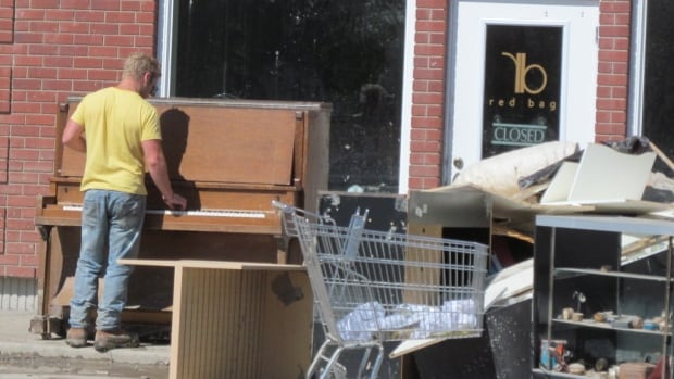 """Angela Piovesana's son and business partner, Derek Adduono, plays """"sad songs on our destroyed piano on the sidewalk after a long day of clearing out the damaged goods,"""" writes Piovesana."""