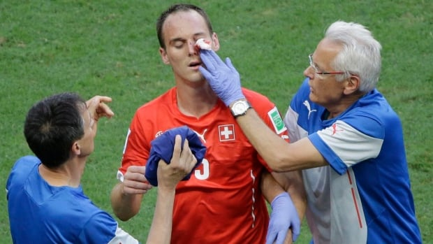 Switzerland's Steve von Bergen, centre, gets treatment after being injured during the group E World Cup soccer match against and France on Friday.