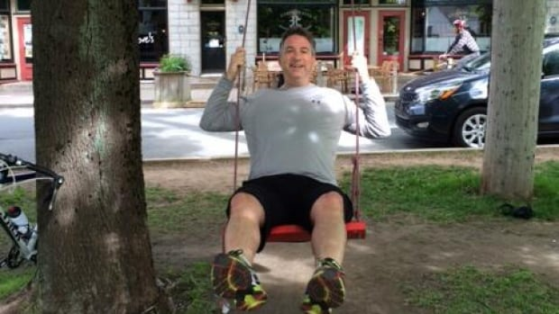 Halifax CAO Richard Butts tries out a red swing Saturday near the Hydrostone Market.