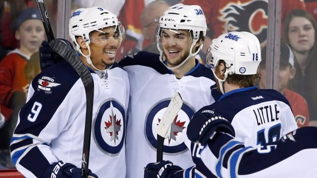 The Winnipeg Jets' Michael Frolik, centre, celebrates a goal against the Calgary Flames on April 11 with Evander Kane, left, and Bryan Little.