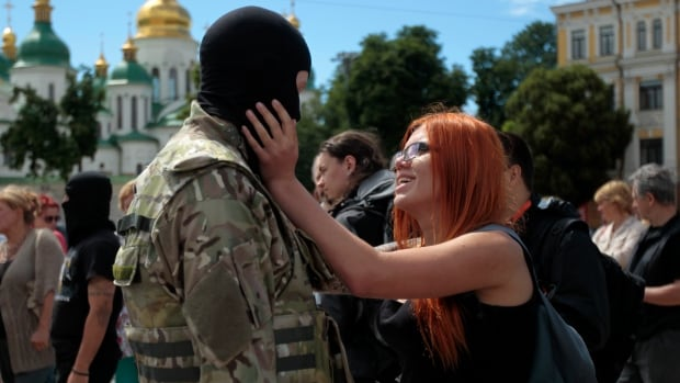 A girl says goodbye to her friend before he was sent to the eastern part of Ukraine to join the ranks of a special battalion, during a ceremony to take the oath of allegiance to Ukraine in Kyiv. Peace talks involving Ukraine, Russia and pro-Russian rebels are underway in Donetsk.