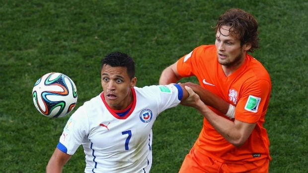 Alexis Sanchez of Chile, left, fights off Daley Blind of the Netherlands during the teams' match at the 2014 FIFA World Cup.