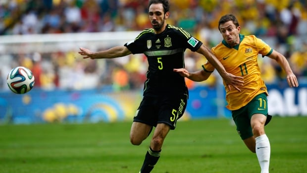 Spain's Juanfran fights for the ball with Australia's Tommy Oar during Monday's FIFA World Cup match at the Baixada arena in Curitiba,