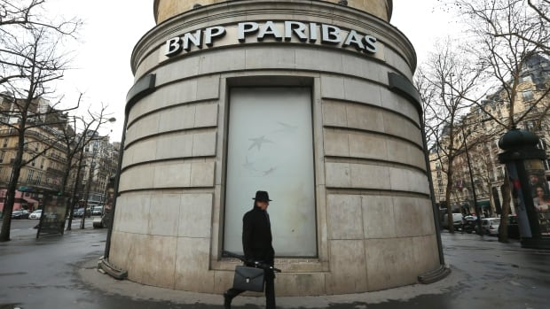 A man walks past the French bank BNP Paribas headquarters in Paris. The bank faces a ban on U.S. dollar trading for a year as part of its penalty for violating U.S. sanctions.
