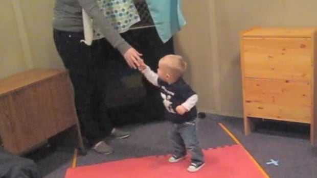 """A baby helps out a new friend after the researcher and lead author, Laura Cirelli, """"accidentally"""" drops a clothes pin. The toddler, who just """"danced"""" with Cirelli for less than three minutes before the test, helps her our by picking up the dropped pin."""