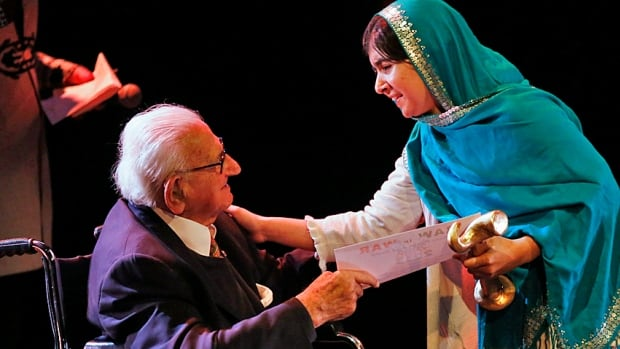 Still the humanitarian, Nicholas Winton presents Pakistan's Malala Yousafzai with the Reach All Women in War award in London in October 2013. Yousafzai is the Pakistani girl shot by the Taliban in 2012 for standing up for her right to an education.