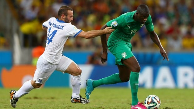 Yaya Toure of the Ivory Coast, right, controls the ball against Dimitris Salpingidis of Greece during the teams' match during the FIFA World Cup in Brazil.