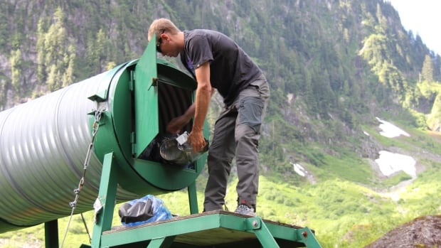 A volunteer with the North Shore Rescue team repacks the looted Hanes Valley Cache.