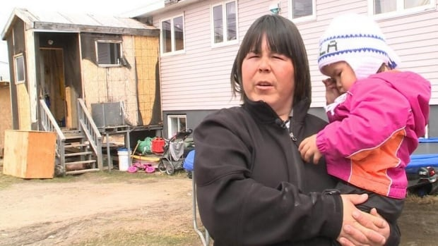 Connie Pijogge holds her daughter Jayla outside of their family rental home in Nain. With nowhere to go, Pijogge and her family will be forced to move in with relatives, or out of the community.