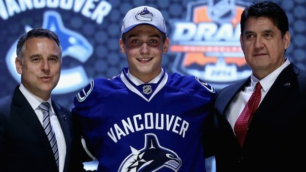 Jake Virtanen, middle, is seen after being selected sixth overall by the Vancouver Canucks at the 2014 NHL draft.