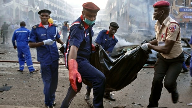 Rescue workers carry human remains in a body bag after an explosion at a shopping mall in Abuja, Nigeria on June 25.