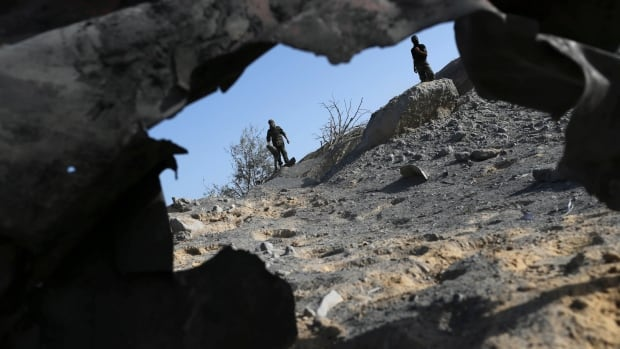 Palestinian militants inspect what police said was the aftermath of an Israeli air strike in Khan Younis in the southern Gaza Strip.