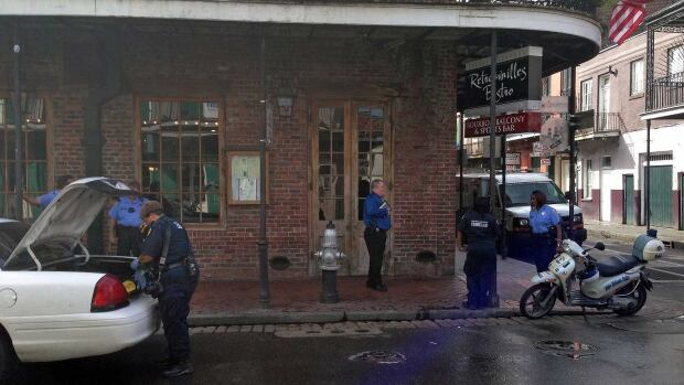 Authorities continue working the scene along Bourbon Street after a shooting early Sunday.