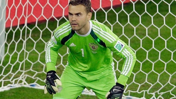 Russia's goalkeeper Igor Akinfeev is shown with a green laser dot on his shoulder during the group H World Cup soccer match between Algeria and Russia at the Arena da Baixada in Curitiba, Brazil, Thursday, June 26, 2014. (AP Photo/Michael Sohn)
