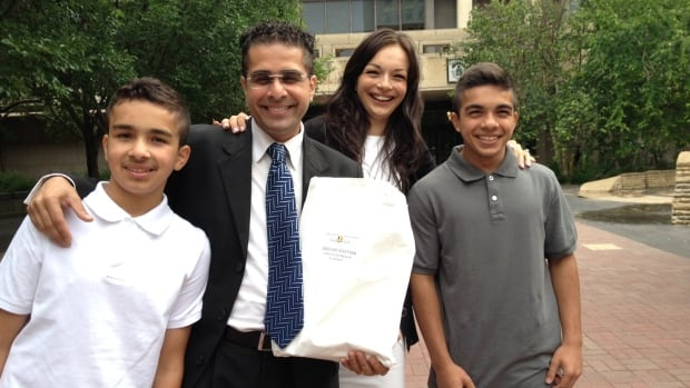 Sachit Mehra, second from left, stands with his wife, Caroline, and sons Mohit and Givan as he registers as a city council candidate in the St. Norbert ward on Monday.