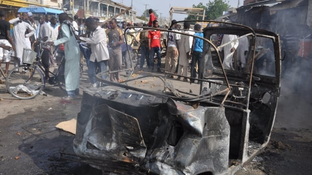 People gather at the scene of a car bomb explosion at the central market in Maiduguri, Nigeria, on Tuesday. Dozens are feared dead in the latest explosion linked to the Islamic extremist group Boko Haram.