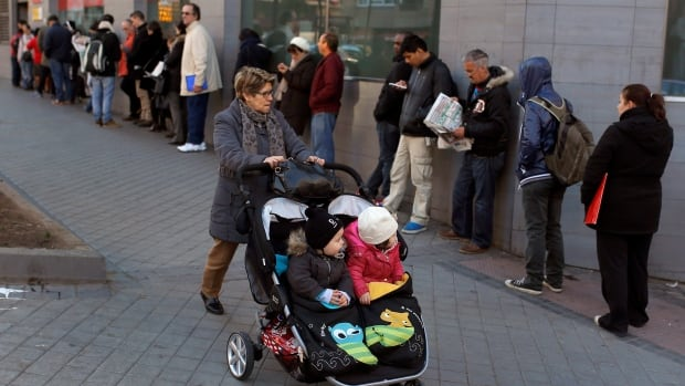 People queue to enter an unemployment registry office in Madrid, Spain, Tuesday, March 4, 2014.  Spain's unemployment rate tops 25 per cent.