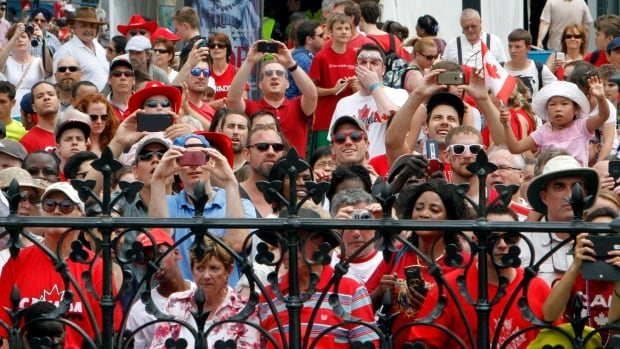 Crowds of people peer over gates of Parliament Hill to get photos and a look at dignitaries and Canada Day celebrations on Parliament Hill in Ottawa, Tuesday July 1, 2014.