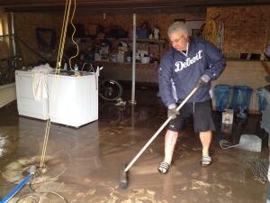 Richard Naujokes cleans up garage flooding