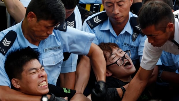 Protesters are taken away by police officers after hundreds of protesters staged a peaceful sit-ins overnight on a street in the financial district in Hong Kong Wednesday.