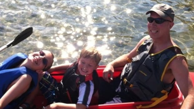 Detroit amateur soccer referee John Bieniewicz sits in the stern of a kayak with his two young sons. He died Tuesday after being struck by a player. His death has prompted an outpouring of concern.