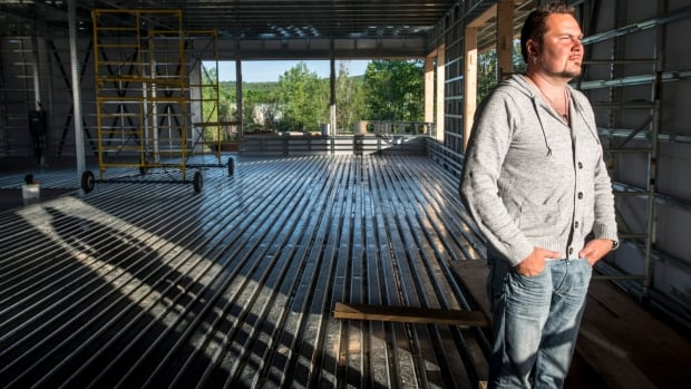 Yannick Gagne stands in the new Musi-Café under construction Wednesday, June 11, 2014 in Lac-Mégantic, Que. Gagné, owner of the popular hang-out, still pictures the faces of the people at his bustling Quebec bar last summer, many of whom vanished when an oil-filled train screeched off the nearby tracks and exploded in Lac-Mégantic.