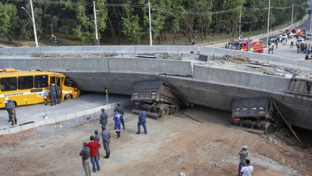 Rescue workers try to reach vehicles trapped underneath a bridge that collapsed while under construction in Belo Horizonte, July 3, 2014. An unfinished overpass collapsed in the Brazilian World Cup host city of Belo Horizonte on Thursday, killing at least two people, emergency officials said.