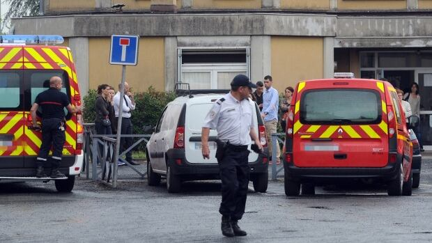 Policemen and firemen are seen in front of the primary school Edouard-Herriot where a female teacher was stabbed to death in front of her pupils by a student's mother on Friday in the southern French town of Albi.